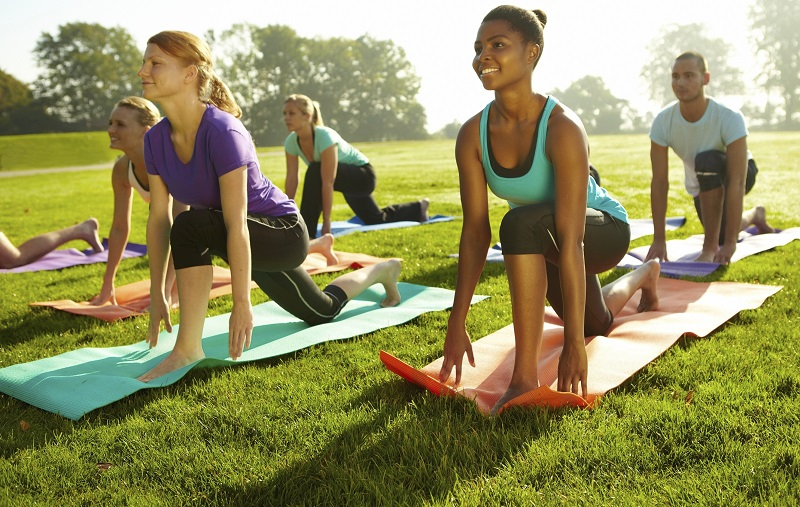 Group of young people doing a yoga class outdoors on a green field