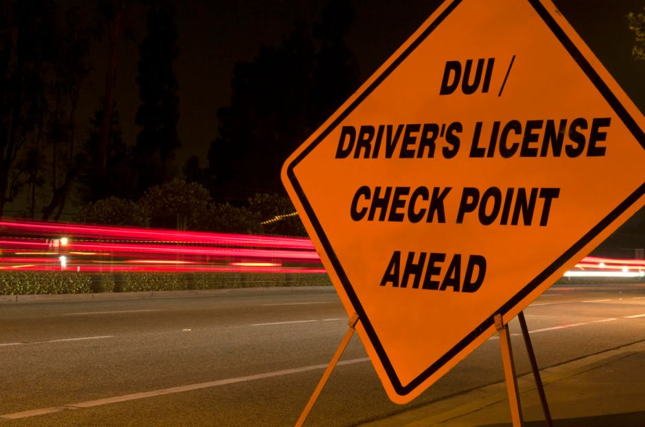 Orange DUI 'sobriety' and driver's license checkpoint ahead sign along side of road with car light trails in background